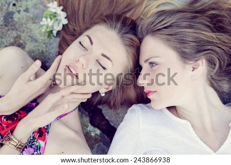 Closeup portrait of calm pretty girl friends lying down on stone abstract background - stock photo