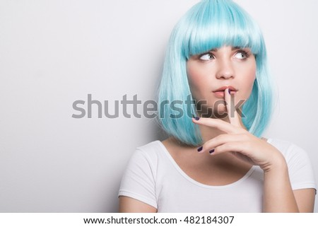 Closeup portrait of cheeky young girl in modern futuristic style wearing blue wig with curious expression and finger on lip while looking sideways over white wall background with copyspace