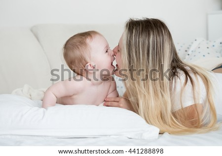 Closeup portrait of cheerful baby with mother lying on big white pillow - stock photo