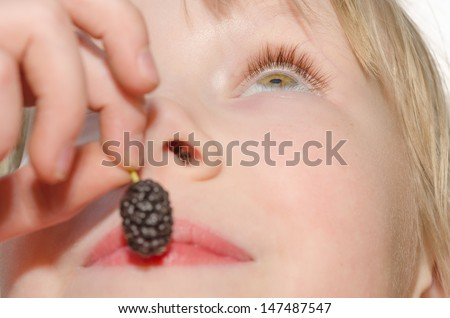 Closeup portrait of cheerful girl, holding in hand and eating mulberry fruit