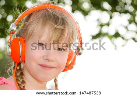 Closeup portrait of cheerful girl listening lesson in headphones against white green bokeh background - stock photo