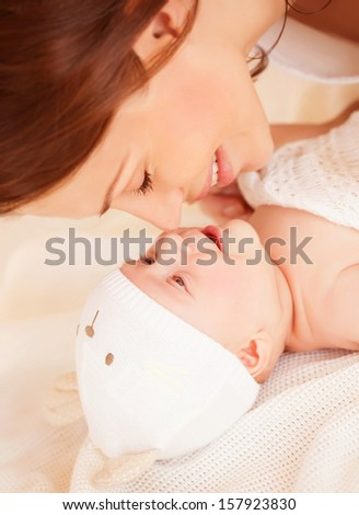 Closeup portrait of cheerful young mother with adorable newborn baby having fun at home, child care, happy parenthood, love concept