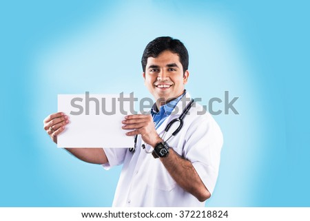 Closeup portrait of confident indian healthcare professional or doctor or nurse with stethoscope, holding up business card, copy space, indian male doctor with blank card, isolated on blue background - stock photo