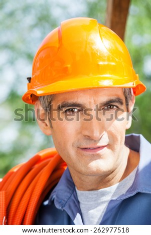 Closeup portrait of confident male construction worker wearing hardhat at site - stock photo