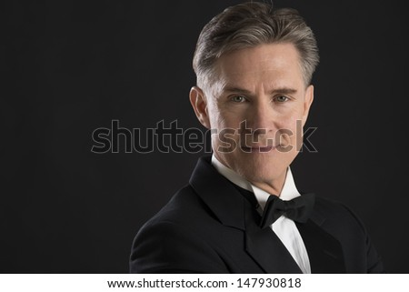 Closeup portrait of confident mature man in tuxedo isolated on black background - stock photo