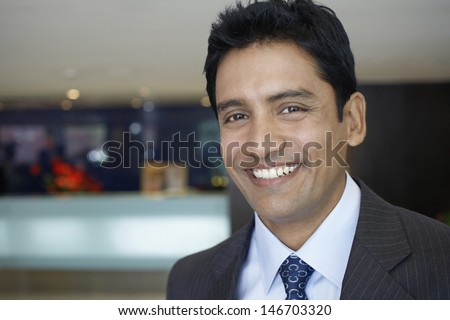Closeup portrait of confident young businessman smiling in hotel lobby - stock photo