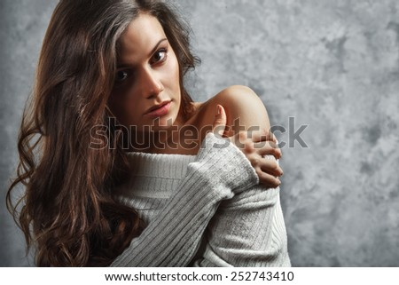 closeup portrait of curly beautiful female model on gray background - stock photo