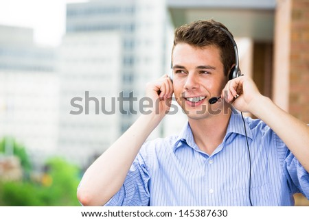 Closeup portrait of customer service representative or call center agent or support staff or operator with headset on outside balcony, isolated on outside background with trees and city buildings