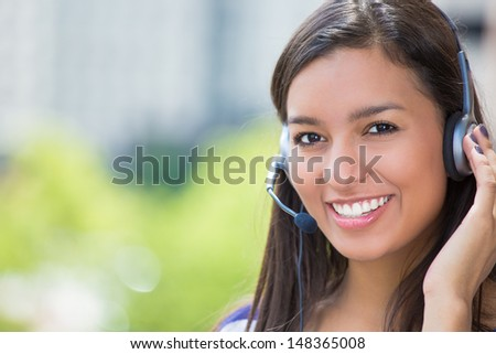 Closeup portrait of customer service representative or call center agent or support staff or operator with headset on outside balcony, isolated on outside background with trees and city buildings - stock photo