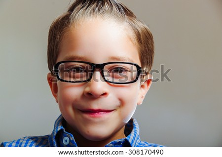 closeup portrait of cute adorable boy wearing glasses over gray background - stock photo