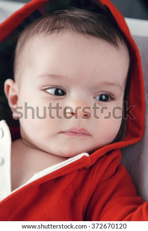 Closeup portrait of cute adorable Caucasian baby boy girl with black brown eyes in red hoodie shirt on changing table looking away from camera, natural light indoors