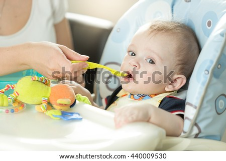 Closeup portrait of cute adorably baby boy sitting in chair and eating from spoon - stock photo