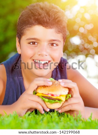 Closeup portrait of cute arabic boy eating burger outdoors, lying down on green grass and enjoying picnic in the park in summer, happy childhood concept   - stock photo