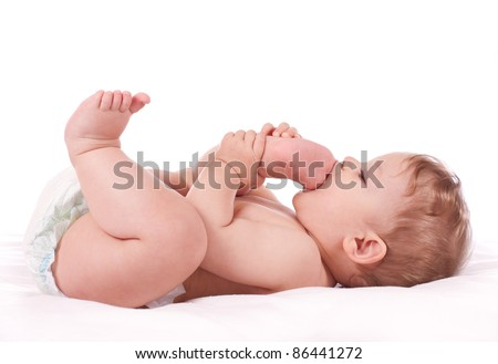Closeup portrait of cute baby boy taking his feet in his mouth