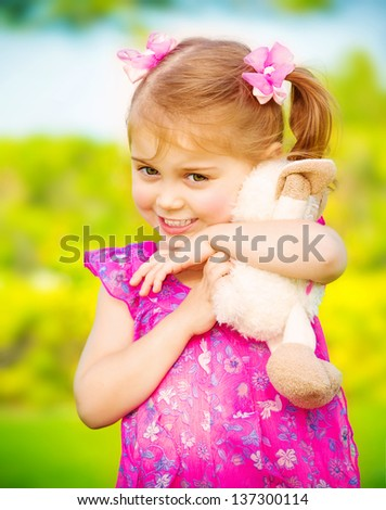Closeup portrait of cute baby girl hugging soft toy outdoors, having fun on backyard in daycare, spring season, happiness concept - stock photo