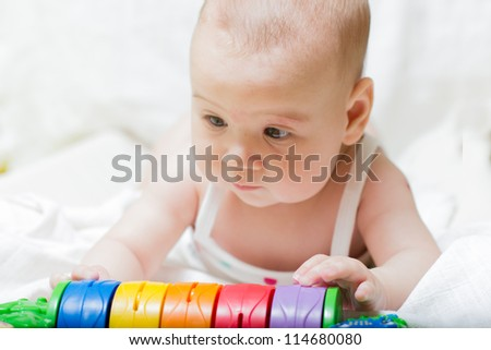 Closeup portrait of cute baby girl playing with toys.