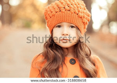 Closeup portrait of cute baby girl wearing knitted hat and winter jacket outdoors. Looking at camera. Childhood. Seasonal.  - stock photo