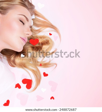 Closeup portrait of cute blond female with closed eyes lying down on pink background with copy space, little red hearts decoration, dreamy Valentines day