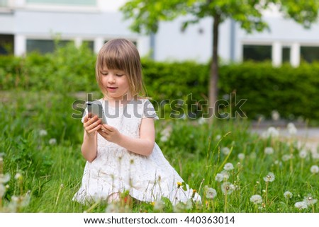 closeup portrait of cute blond girl in preschool age sitting in green grass and holding and playing with mobile phone outdoors - stock photo