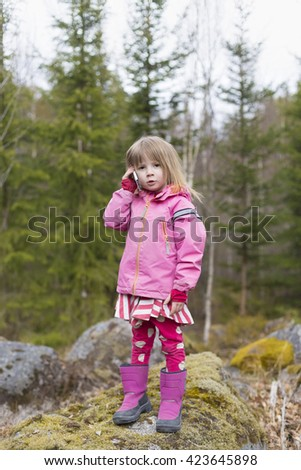 closeup portrait of cute blond girl in preschool age wearing pink jacket and talking by mobile phone outdoors