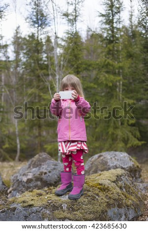 closeup portrait of cute blond girl in preschool age wearing pink jacket holding a mobile phone outdoors