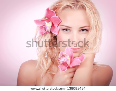 Closeup portrait of cute blond girl with pink orchid flowers isolated, luxury spa salon, natural cosmetics, beauty concept - stock photo