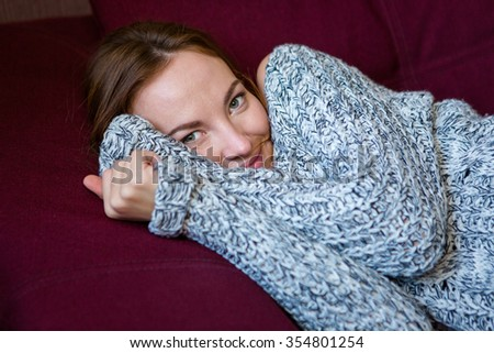 Closeup portrait of cute charming young woman in grey knitted sweater lying on maroon sofa - stock photo