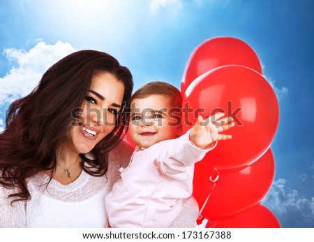 Closeup portrait of cute cheerful mother carry sweet baby daughter, having fun outdoors, playing with red balloons, happy family portrait - stock photo
