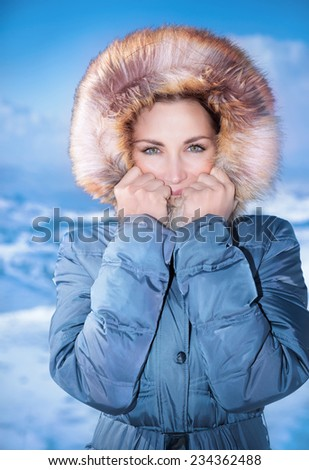 Closeup portrait of cute female outdoors in winter time, wearing stylish casual blue coat with furry hood, winter fashion concept - stock photo