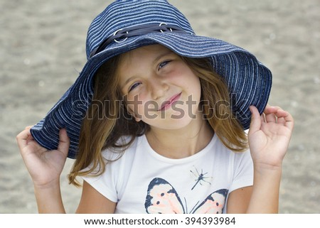 Closeup portrait of cute girl in hat on the beach - stock photo