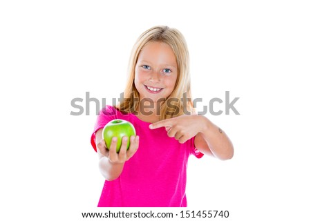 Closeup portrait of cute girl showing delicious green apple by pointing with finger, isolated on white background