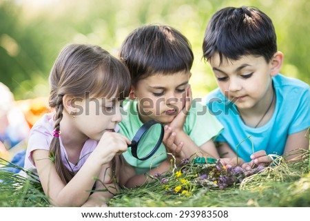 closeup portrait of cute kids with magnifying glass outdoors - stock photo