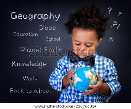 Closeup portrait of cute little African boy with small globe in hands, preparing to geography lesson, back to school concept - stock photo