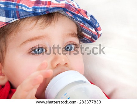 Closeup portrait of cute little boy with big blue eyes eating, drinking milk from bottle, healthy nutrition for kids, tasty baby food - stock photo