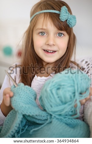 Closeup portrait of cute little girl knitting with knitting-needle at home - stock photo