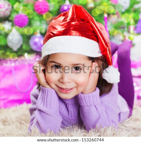Closeup portrait of cute little girl lying down on carpet under beautiful decorated Christmas tree at home, winter holidays, New Year celebration