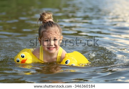 Closeup portrait of cute little girl swimming, happy child having fun in water, beach resort, summer vacation and holidays concept - stock photo