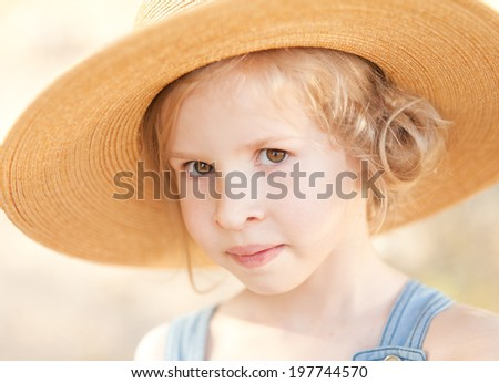 Closeup portrait of cute little girl wearing hat outdoors - stock photo