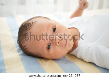 Closeup portrait of cute newborn baby lying in bed