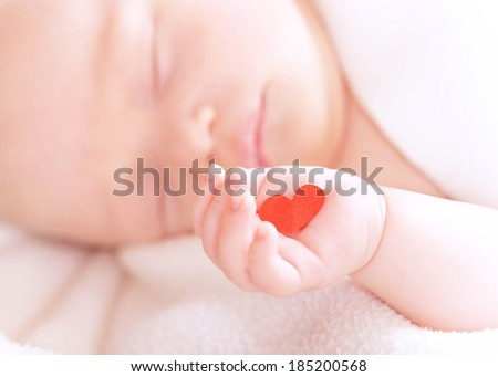 Closeup portrait of cute newborn baby sleeping, holding in hand little red heart, innocent child, soft focus, hope and help concept - stock photo