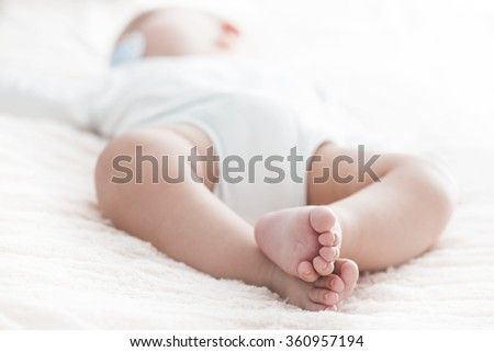 Closeup portrait of cute newborn baby sleeping,innocent child, soft focus, hope and help concept.Selective focus on baby's  foot.