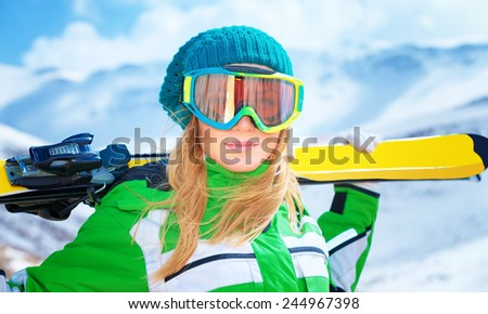 Closeup portrait of cute ski trainer,  active woman wearing a mask and holding in hands ski, active winter vacation, happiness and enjoyment concept  - stock photo