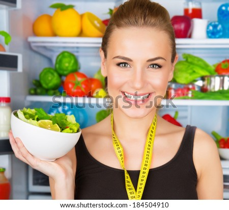 Closeup portrait of cute smiling woman with measure tape and fresh vegetables salad, sportive trainer, organic food, health and beauty care concept  - stock photo