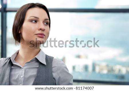 Closeup portrait of cute young business woman smiling and looking away - stock photo