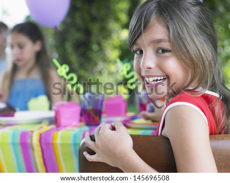 Closeup portrait of cute young girl looking over shoulder outdoors