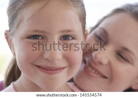 Closeup portrait of cute young girl with loving mother