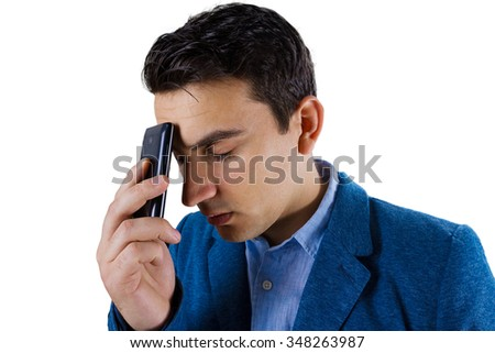Closeup portrait of depressed, worried young man, student holding the phone on his head, isolated on white background.Distress young man talking on phone.