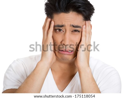 Closeup portrait of depressed young man shaken up crushed by terrible news almost crying, hands on face, isolated on white background. Negative emotion facial expression feelings, reaction, situation - stock photo