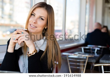 closeup portrait of drinking coffee or tea and working on laptop beautiful cheerful blond young business woman with green eyes having fun relaxing happy smiling and looking into the camera image - stock photo