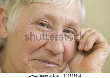 Closeup portrait of elderly woman smiling against beige background